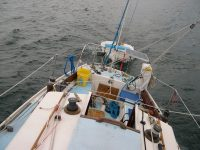"Photo of Sweet Breeze nicely heeled over in a good wind with Curt's self-rigged ""sheet to tiller"" autopilot system working fine."